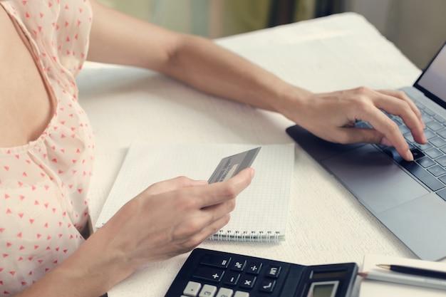 La mujer paga las compras en línea con tarjeta de crédito.