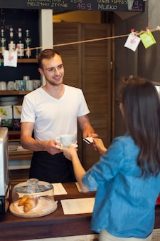 Mujer pagando café con tarjeta de crédito