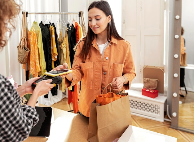 Mujer pagando ropa en tienda