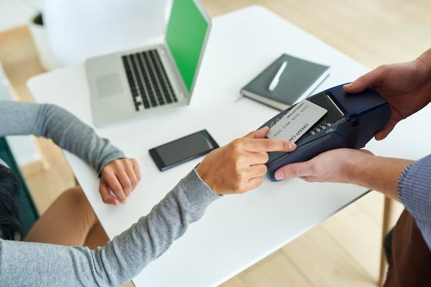 Mujer pagando con tarjeta nfc en cafe