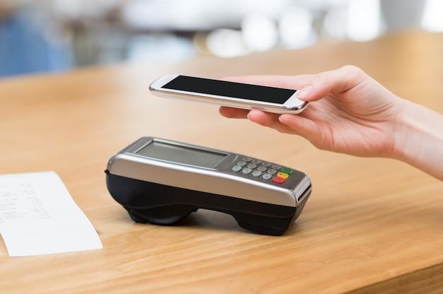 Mujer pagando con tecnología nfc en teléfonos inteligentes.