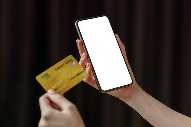 Mujer de pago en línea realiza compras en línea mediante pago con tarjeta de crédito en un teléfono inteligente móvil.