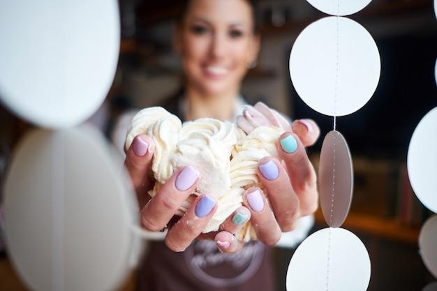 Mujer panadero o pastelero con postre de malvavisco en panadería