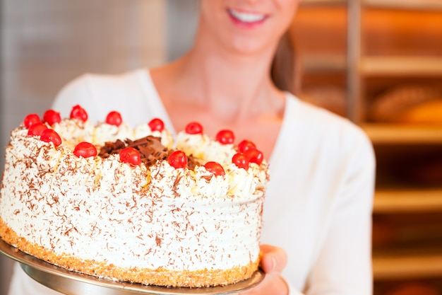 Mujer panadero o pastelero con torta