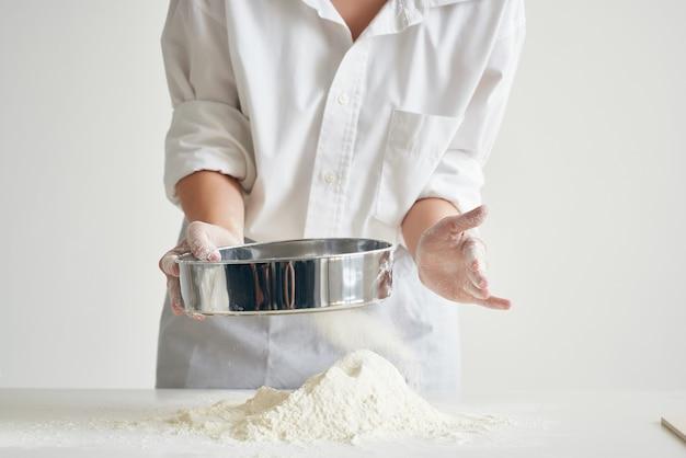 Mujer panadero en uniforme de chef lanza masa harina cocina profesional