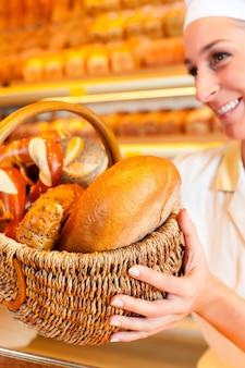 Mujer panadero vendiendo pan por canasta en panadería