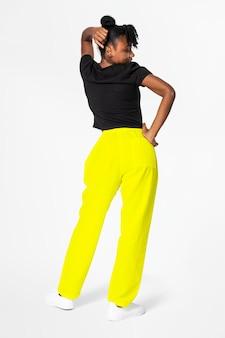 Mujer en pantalones de chándal amarillo neón y camiseta negra vista trasera de ropa de calle