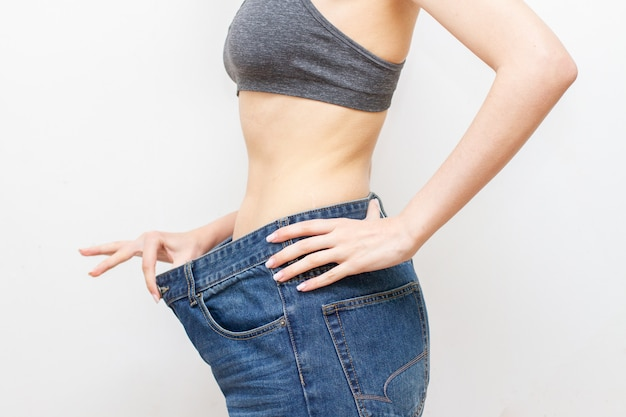 Mujer en pantalones de gran tamaño después de la pérdida de peso. concepto de dieta.