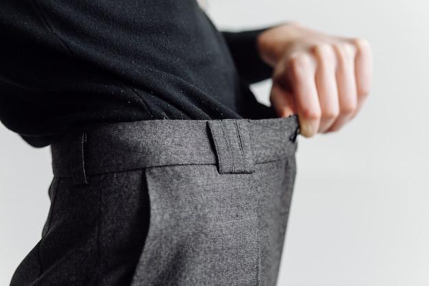 Mujer en pantalones grandes. concepto de pérdida de peso