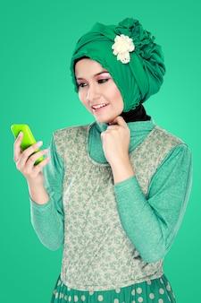 Mujer con pañuelo en la cabeza con teléfono móvil