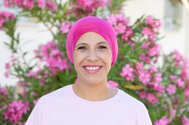 Mujer con pañuelo rosa en la cabeza.
