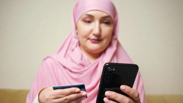 Mujer con un pañuelo rosa hace compras en línea por teléfono con una tarjeta bancaria en las manos.