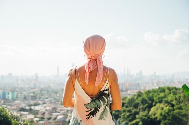 Mujer con pañuelo rosa mirando el horizonte. concepto de cáncer