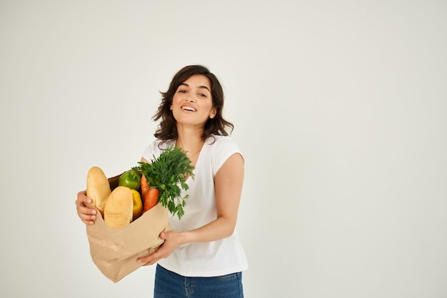 Mujer con un paquete de abarrotes de compras en el supermercado fondo claro