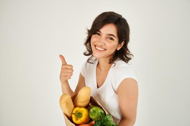 Mujer en paquete de camiseta blanca con abarrotes en el supermercado comida sana