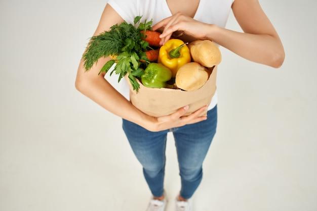 Mujer con paquete de comestibles como verduras vista recortada del supermercado