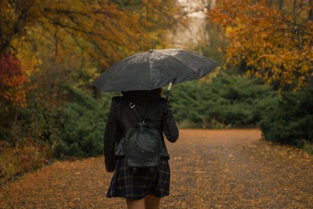 Mujer con un paraguas caminando en el parque en un lluvioso día de otoño