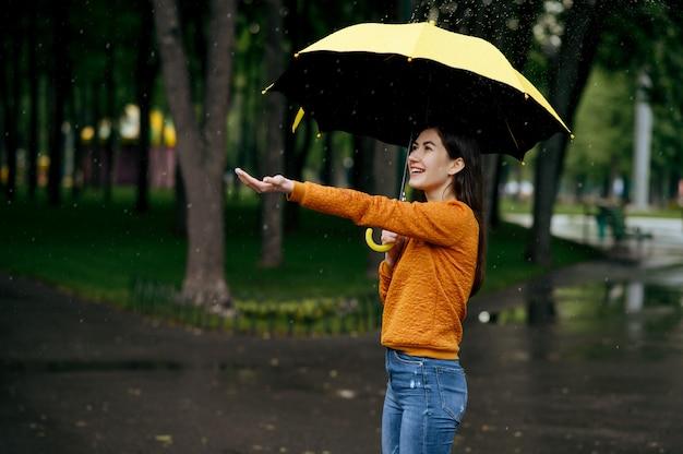Mujer con paraguas disfruta de la lluvia en el parque de verano, día lluvioso. persona de sexo femenino caminando solo, clima húmedo en el callejón