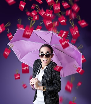 Mujer con paraguas bajo una lluvia de precios en baja