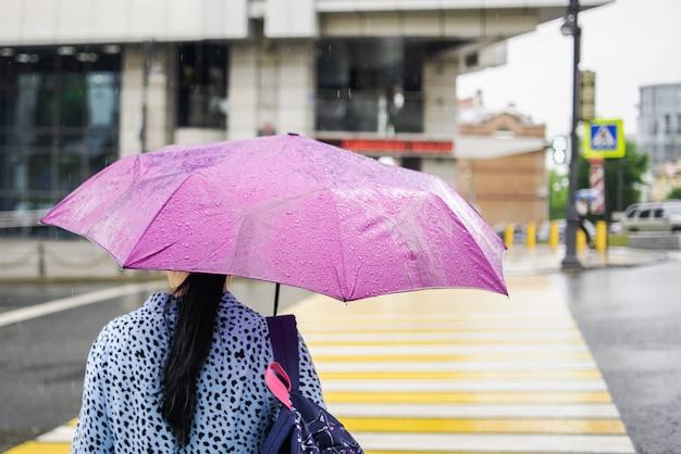 Mujer con un paraguas rosa en tiempo lluvioso cruzando la peatonal.
