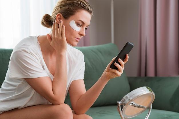 Mujer con parches de máscara de ojo y usando el teléfono móvil