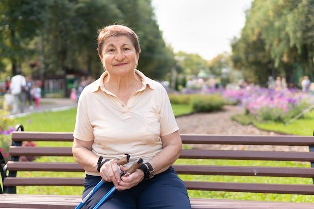 Una mujer en el parque camina con palos en un día soleado de verano