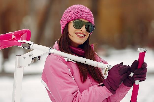 Mujer en un parque de invierno. dama en traje deportivo rosa. mujer con moto de nieve.