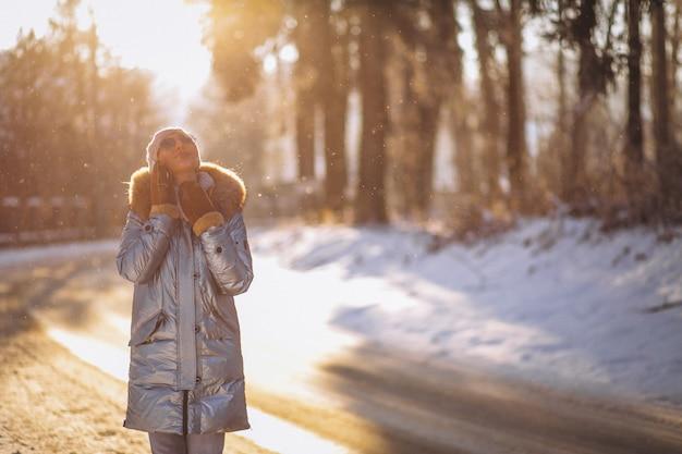 Mujer en un parque de invierno hablando por teléfono