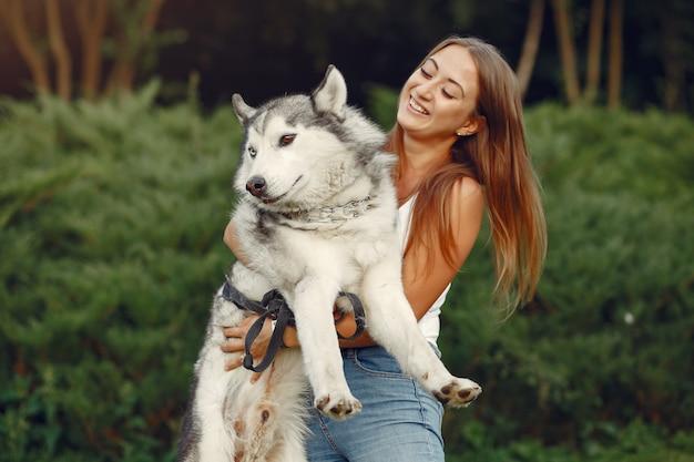 Mujer en un parque de primavera jugando con lindo perro