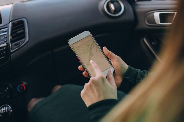 Mujer pasajera en un automóvil con un mapa en un teléfono inteligente prepara una ruta
