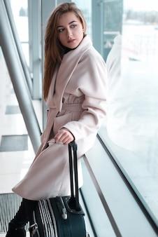 Mujer de pasajero en el aeropuerto esperando el transporte aéreo.