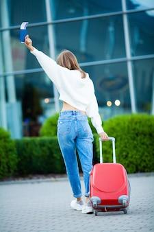 Mujer con pasaporte y boletos cerca del aeropuerto