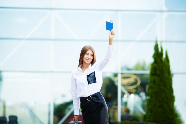 Una mujer con pasaporte y maleta cerca del aeropuerto se va de viaje