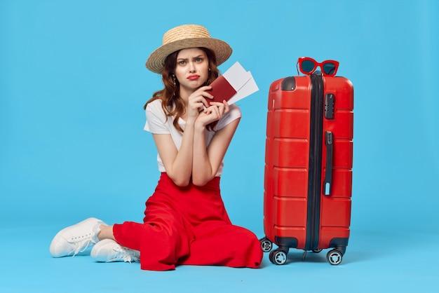 Mujer con pasaporte maleta roja y billetes de avión destino de vacaciones