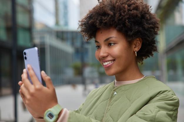 Mujer pasea en un lugar urbano disfruta de blogs y chatear con seguidores en línea disfruta de videollamadas usa poses de chaqueta al aire libre usa aplicación de comunicación
