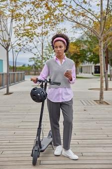 Mujer paseos en scooter eléctrico en la ciudad disfruta de las vacaciones utiliza el teléfono móvil para navegar utiliza el transporte personal ecológico