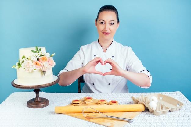 La mujer pastelera pastelera muestra el símbolo del corazón de los dedos junto al pastel de cumpleaños de boda blanco cremoso de dos niveles con flores frescas en la mesa en el estudio sobre fondo azul. el concepto de amor al trabajo