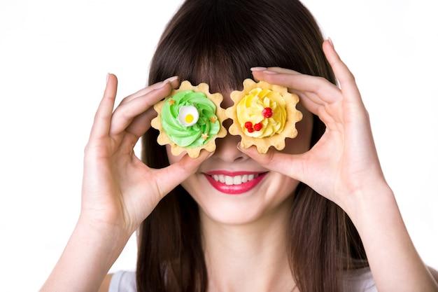 Mujer con pasteles de colores en los ojos