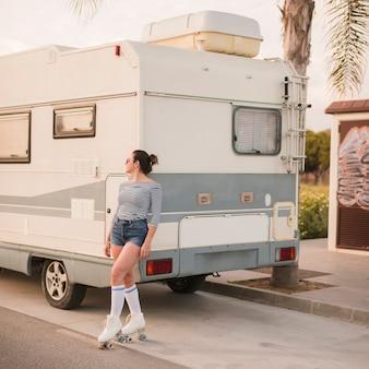 Mujer patinadora inclinada cerca de caravana mirando lejos