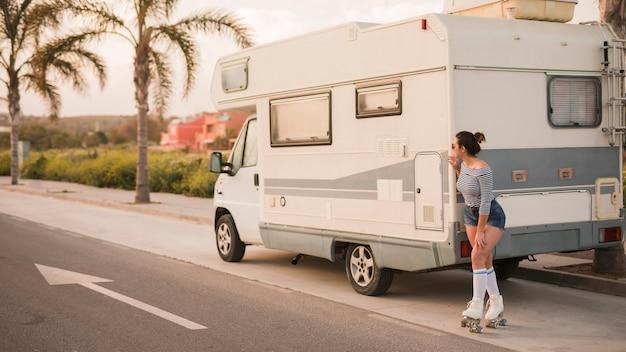 Mujer patinadora de pie detrás de la caravana en la carretera mirando a escondidas