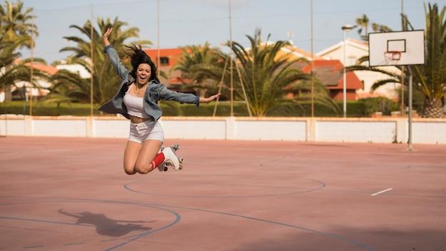 Mujer patinadora saltando por encima de la cancha de fútbol.