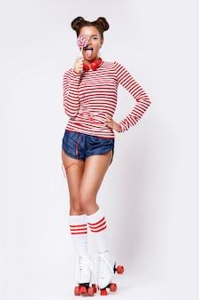 Mujer en patines y con auriculares rojos y piruleta