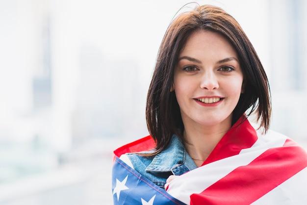 Mujer patriota envuelta en bandera americana