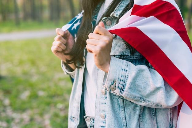 Mujer patriótica con bandera americana en los hombros.