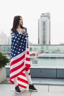 Mujer patriótica envuelta en gran bandera estrellada