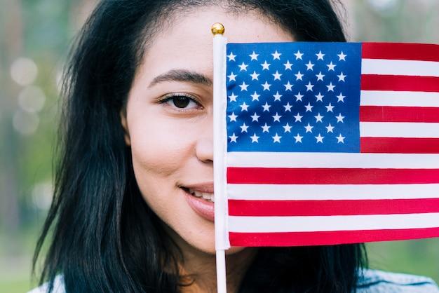 Mujer patriótica que cubre la cara con la bandera de estados unidos