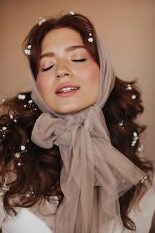 Mujer con pecas posa con los ojos cerrados sobre fondo beige. foto de mujer con pañuelo en la cabeza con flores en el pelo.