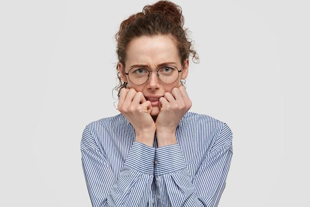 La mujer pecosa nerviosa enojada se muerde las uñas, se ve con expresión hosca, disgustada porque tiene que esperar algo mucho tiempo, vestida con una camisa a rayas, aislada sobre una pared blanca. disgusto