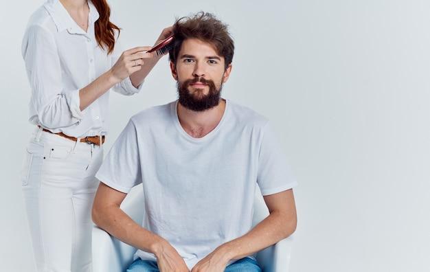 Mujer con peine haciendo pelo al hombre peluquería profesional salón de belleza