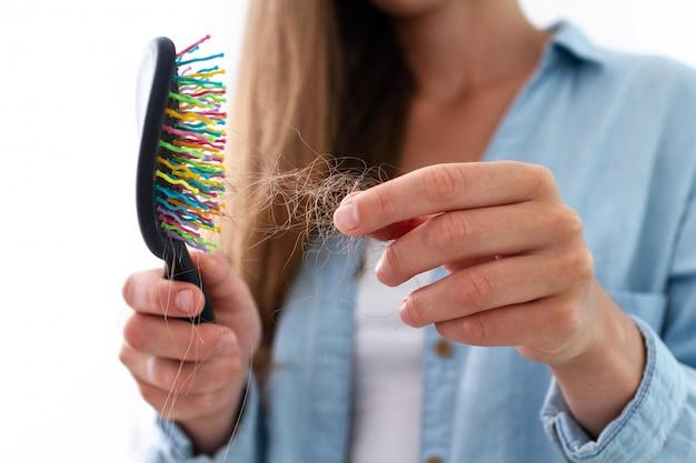 Mujer con peine que sufre pérdida de cabello
